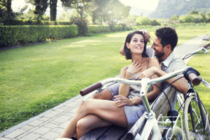 Couple in love joking together on a bench with bikes on vacation