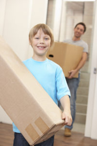 Boy with young man on moving day carrying cardboard box